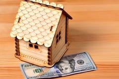Une petite banque maison-porcine en bois et un billet de banque 100 dollars sur a Photographie stock libre de droits