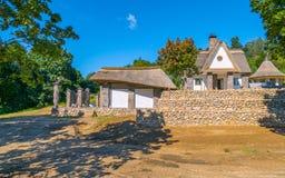 Une petite, belle maison avec un toit tubulaire entouré par une barrière en pierre au milieu de la forêt Photo libre de droits