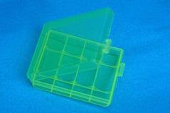 Une petite boîte en plastique verte ouverte est sur une table bleue images stock