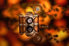 Une petite broche sous forme de caméra sur un fond orange photographie stock