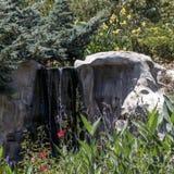 Une petite cascade artificielle entre de grandes pierres Photo stock