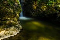 Une petite cascade de gouttière cachée derrière les falaises moussues dans la forêt Photos stock