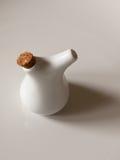 Une petite et blanche petite bouteille d'huile avec deux trous sur le bec a Photo libre de droits