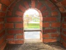 Une petite fenêtre étroite sur un mur de briques épais de vieille pierre antique dans un vieux château Le fond photographie stock libre de droits