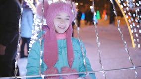 Une petite fille à une foire de Noël au centre de la ville, entouré par des guirlandes et des lumières pour avoir l'amusement banque de vidéos