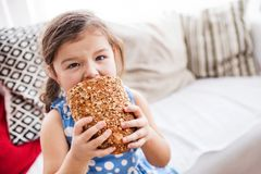 Une petite fille à la maison mangeant une miche de pain Image libre de droits