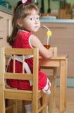 Une petite fille à une table Photo stock