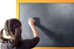 Une petite fille écrit sur un tableau noir Photos libres de droits