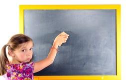 Une petite fille écrit sur un tableau noir Images libres de droits