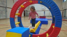Une petite fille équilibrant sur une poutre de gymnastique pensant à sa prochaine étape images stock