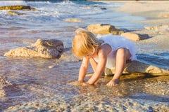 Une petite fille adorable mignonne d'enfant en bas âge dans des vêtements blancs jouant avec le sable et les coquilles sur la pla Photos stock