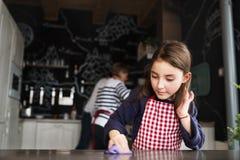 Une petite fille aidant dans la cuisine à la maison Photos stock