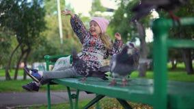 Une petite fille alimente des pigeons en parc d'automne banque de vidéos