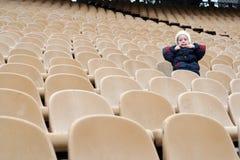 Une petite fille a une ans dans les fans vides que la zone sur le stade fait des grimaces image stock