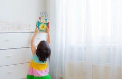 Une petite fille 3 ans de bouts droits pour obtenir un jouet éducatif d'une haute étagère Photos libres de droits