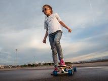Une petite fille apprend à patiner sur un grand longboard en parc pour le patinage photos libres de droits