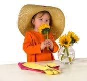 Une petite fille arrangeant des fleurs sur la table Images libres de droits