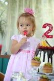 Une petite fille aux cheveux blancs de deux ans essaye un gâteau d'anniversaire Petite fille célébrant le deuxième anniversaire Image libre de droits
