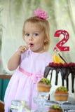 Une petite fille aux cheveux blancs de deux ans essaye un gâteau d'anniversaire Petite fille célébrant le deuxième anniversaire Photos libres de droits