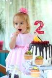 Une petite fille aux cheveux blancs de deux ans essaye un gâteau d'anniversaire Petite fille célébrant le deuxième anniversaire Photos stock