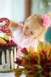 Une petite fille aux cheveux blancs de deux ans essaye un gâteau d'anniversaire Petite fille célébrant le deuxième anniversaire Photographie stock