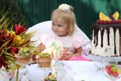 Une petite fille aux cheveux blancs de deux ans essaye un gâteau d'anniversaire Petite fille célébrant le deuxième anniversaire Images libres de droits