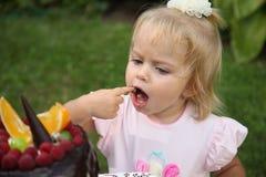 Une petite fille aux cheveux blancs de deux ans essaye un gâteau d'anniversaire Petite fille célébrant le deuxième anniversaire Images stock