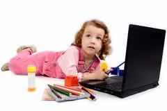 Une petite fille avec l'ordinateur Photographie stock libre de droits