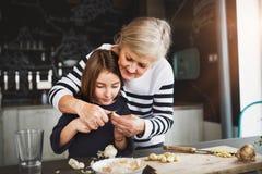 Une petite fille avec la grand-mère faisant cuire à la maison Photo stock