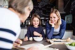 Une petite fille avec la mère et la grand-mère à la maison Images stock