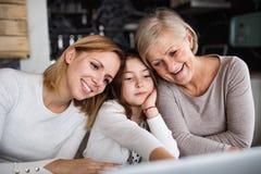 Une petite fille avec la mère et la grand-mère à la maison Photographie stock libre de droits