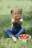 Une petite fille avec les baies rouges lumineuses dans le plat blanc sur Image stock