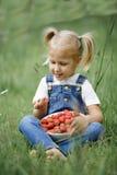 Une petite fille avec les baies rouges lumineuses dans le plat blanc sur Photographie stock