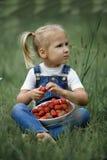 Une petite fille avec les baies rouges lumineuses dans le plat blanc sur Photos libres de droits