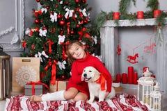 Une petite fille avec un golden retriever de chiot sur un fond d'arbre de Noël Photos libres de droits