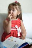 Une petite fille avec un livre Images stock