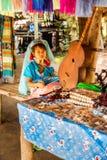 Une petite fille avec un long cou et anneaux sur sa soie de fabrication dans le long village de cou photographie stock