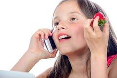 Une petite fille avec un téléphone portable Images stock