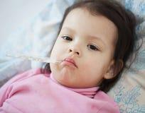 Une petite fille avec un thermomètre Image stock