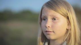 Une petite fille avec un visage triste regarde en avant banque de vidéos
