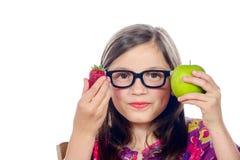 Une petite fille avec une pomme et une fraise Photos libres de droits
