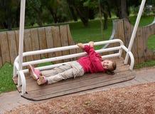 Une petite fille balançant sur une oscillation en parc Photo libre de droits