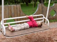 Une petite fille balançant sur une oscillation en parc Photos libres de droits