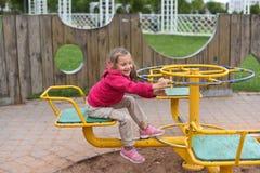 Une petite fille balançant sur une oscillation en parc Photos stock