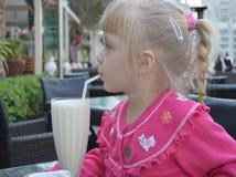 Une petite fille blonde boit d'un milkshake irritable photographie stock