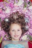Une petite fille blonde se trouvant sur un tissu en soie rose avec une guirlande de Noël et un Noël joue autour de sa tête Images stock