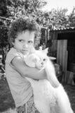 Une petite fille bouclée tient un chat blanc Phot noir et blanc Image stock