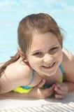 Une petite fille caucasienne heureuse souriant sur la piscine de rebord d'un camping Photographie stock libre de droits