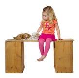 Une petite fille choyant des chiots Photographie stock libre de droits