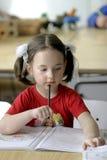 Une petite fille concentrée Photo stock